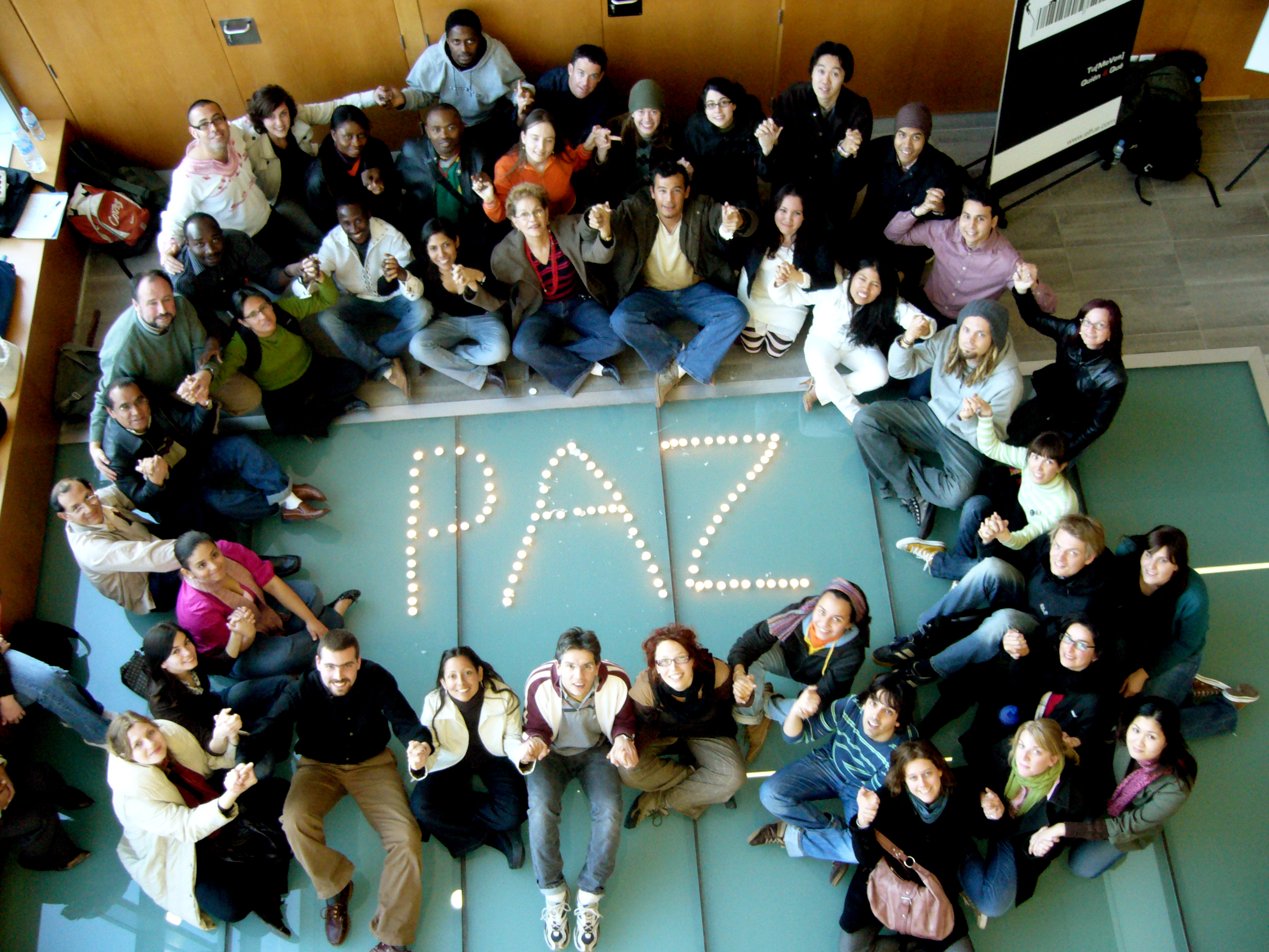 Picture showing university students sitting around the word peace written with candles